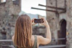 La jeune femme prend une photo d'un ch?teau image stock