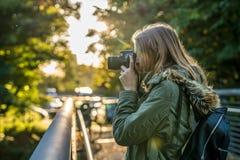 La jeune femme prend une photo de la nature photos stock
