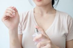 La jeune femme pulvérise le parfum sur son poignet image libre de droits