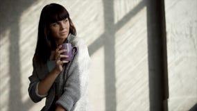 La jeune femme réfléchie romantique s'assied dans sa maison, tenant la tasse de thé clips vidéos