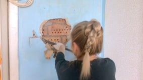La jeune femme répare dans l'appartement Le travailleur un outil de bricolage interrompt un vieux revêtement mural sous lequel banque de vidéos