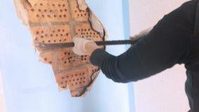 La jeune femme répare dans l'appartement Le travailleur un outil de bricolage interrompt un vieux revêtement mural sous lequel clips vidéos