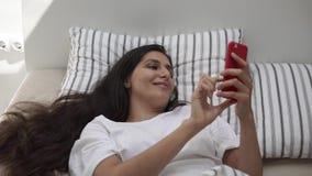 La jeune femme réveillée introduit des messages sur son smartphone, se situant dans le lit clips vidéos