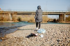 La jeune femme rassemblant les d?chets en plastique de la plage et les mettant dans les sachets en plastique noirs pour r?utilise photos stock