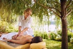 La jeune femme recevant le plein massage de corps au salon de station thermale professent image libre de droits