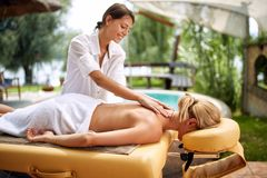 La jeune femme recevant le plein massage de corps au salon de station thermale professent photo stock