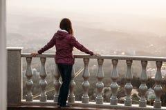 La jeune femme regarde de la plate-forme d'observation la ville en brouillard images stock