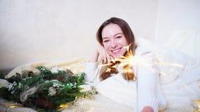 La jeune femme renversante sent l'approche de la nouvelle année et fait le souhait, se trouvant sur le plancher couvert par la co banque de vidéos