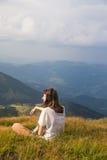 La jeune femme repose le dessus de la colline en montagnes carpathiennes et écoute musique dans des écouteurs appréciant le beau  Photographie stock