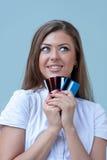 La jeune femme retient des cartes de crédit et sourit Photo stock