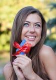 La jeune femme retient un par la carte de crédit et sourit Photo stock