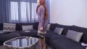 La jeune femme reviennent à la maison et se trouvent au sofa de la fatigue jetant le sac clips vidéos