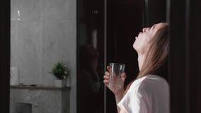 La jeune femme rince sa bouche avec de l'eau et regarder le miroir banque de vidéos