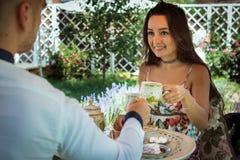 La jeune femme romantique s'assied ainsi que l'ami à la table Photographie stock libre de droits