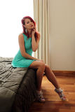 La jeune femme rousse dans la robe verte se reposant sur le lit Image stock