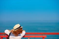 La jeune femme rousse dans le chapeau sur le pilier regarde dans l'océan Image stock