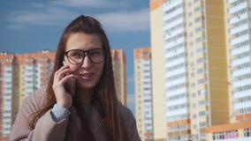 La jeune femme sûre dans une robe élégante se tient contre les bâtiments et parle par le téléphone clips vidéos