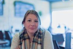 La jeune femme s'asseyant au restaurant, bras a croisé regarder la caméra images stock