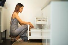 La jeune femme s'asseyent sur le genou dans son placard ouvert de cuisine et trouvent à photo libre de droits