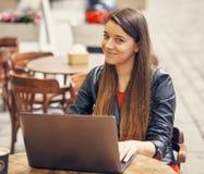 La jeune femme s'asseyent sur la table en bois travaillant sur l'ordinateur Photographie stock libre de droits