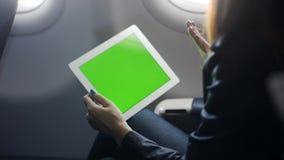 La jeune femme s'assied à l'avion et parle avec l'ami ou l'associé par conférence en ligne sur le comprimé banque de vidéos