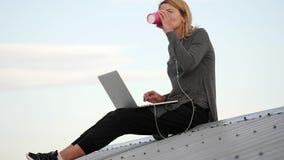 La jeune femme s'assied avec l'ordinateur portable et la musique de écoute sur des écouteurs sur le dessus de toit clips vidéos