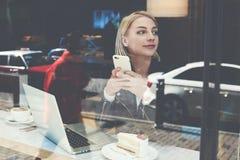 La jeune femme s'assied dans la café-barre moderne avec l'ordinateur portable et le téléphone portable portatifs Photographie stock