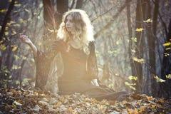 La jeune femme s'assied dans le bois féerique image stock