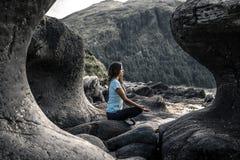 La jeune femme s'assied parmi les pierres de courbe en Norvège Photo libre de droits