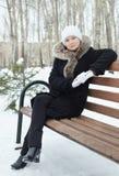 La jeune femme s'assied sur le banc en bois en parc d'hiver Photos libres de droits