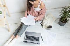 La jeune femme s'assied sur le plancher dans un int?rieur scandinave d'appartement avec un ordinateur portable, ?tudiant la loi,  photos libres de droits