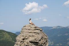 La jeune femme s'assied sur une roche dans la zone rurale de montagne le jour ensoleillé d'été et apprécie le beau paysage Photos libres de droits