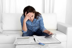 La jeune femme s'est inquiétée à la maison en papiers de banque de comptabilité d'effort avec la calculatrice photo stock