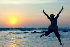 La jeune femme sautant avec joie au-dessus de l'eau photos libres de droits