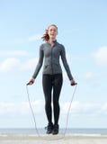 La jeune femme sautant avec la corde à sauter dehors Photographie stock libre de droits