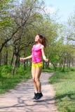 La jeune femme sautant avec une corde à sauter dans un résumé Photos stock