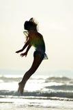 La jeune femme sautant sur la plage dans le coucher du soleil d'été Images libres de droits