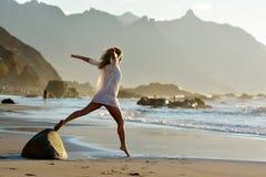 La jeune femme sautant sur la plage en été Image stock