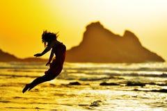 La jeune femme sautant sur la plage en été images stock