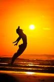 La jeune femme sautant sur la plage en été Images libres de droits