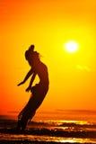 La jeune femme sautant sur la plage en été photos stock
