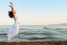 La jeune femme saute sur le littoral Photographie stock libre de droits