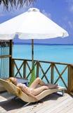 La jeune femme se bronze sur la villa sur l'océan Maldives Images stock