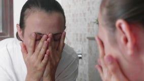 La jeune femme se lave le visage devant le miroir dans la salle de bains banque de vidéos