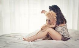 La jeune femme se repose avec un chien de caniche sur le lit Photos stock