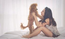 La jeune femme se repose avec un chien de caniche sur le lit Photographie stock