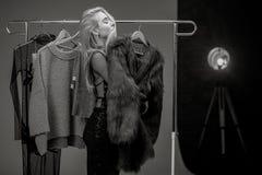 La jeune femme se tient à côté du support avec des cintres et des rêves au sujet de manteau de fourrure Image noire et blanche images libres de droits