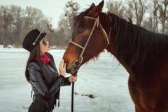 La jeune femme se tient près d'un cheval image libre de droits