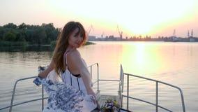 La jeune femme se tient sur l'arc du bateau à voile sur le coucher du soleil de fond dans le voyage d'été clips vidéos