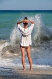La jeune femme se tient sur la plage de mer et regarde Photos stock
